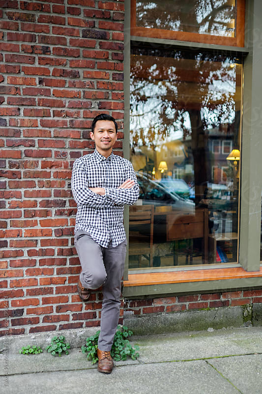 Small business owner standing in front of his store by Suprijono Suharjoto for Stocksy United