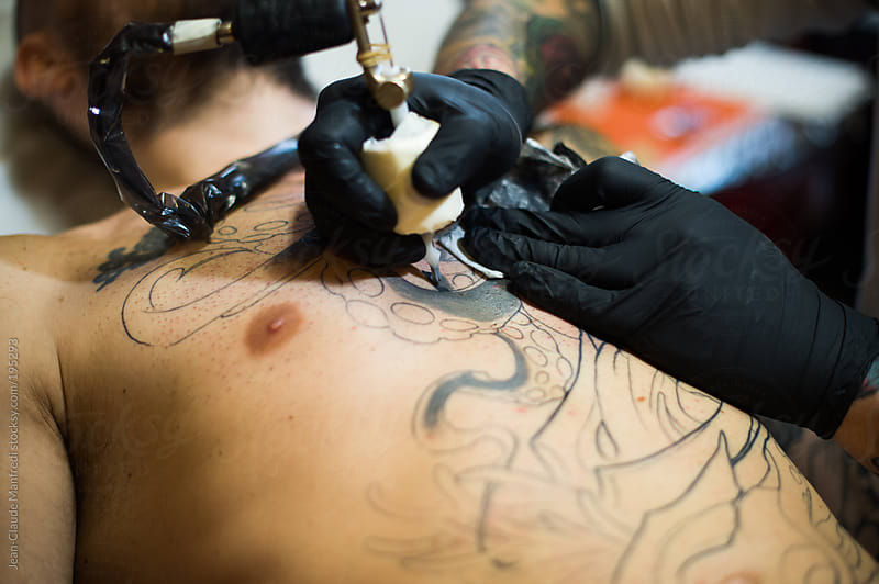 Making Tattoo: a man continue his work in progress tattoo on his chest by Jean-Claude Manfredi for Stocksy United