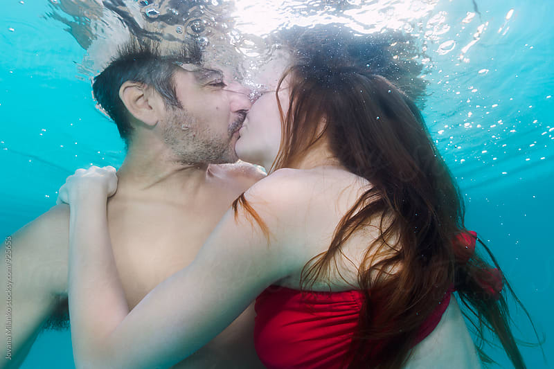 Beautiful couple kissing underwater in the pool by Jovana Milanko for Stocksy United