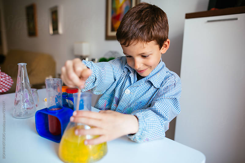 Portrait of a little boy making experiments at home. by BONNINSTUDIO for Stocksy United