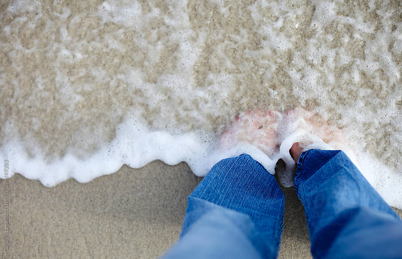 Girl standing in the surf with jeans on and the tide is washing over her feet. by Carolyn Lagattuta for Stocksy United