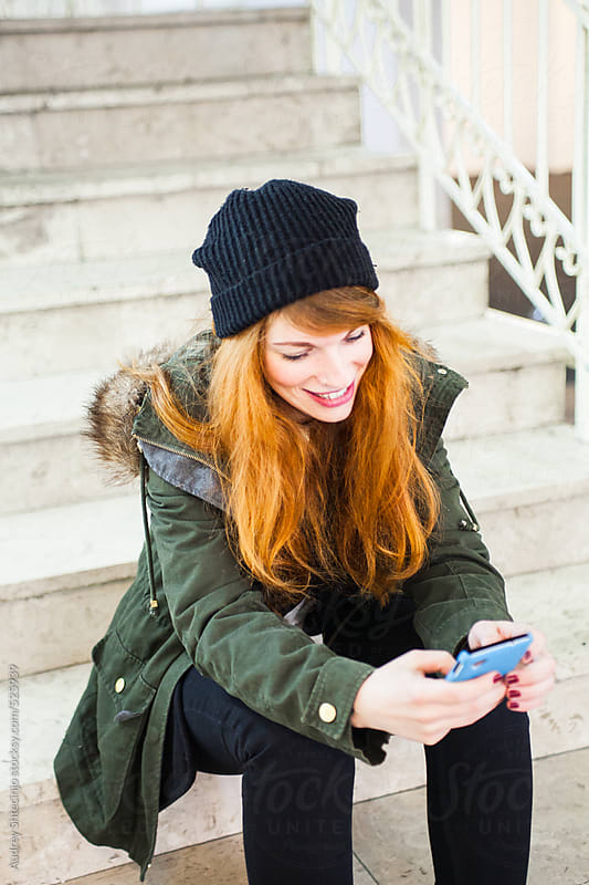 Young red-haired woman typing message on her phone. by Audrey Shtecinjo for Stocksy United
