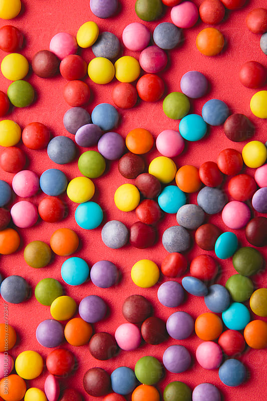 Close up of a pile of colorful chocolate coated candy on red background. by BONNINSTUDIO for Stocksy United