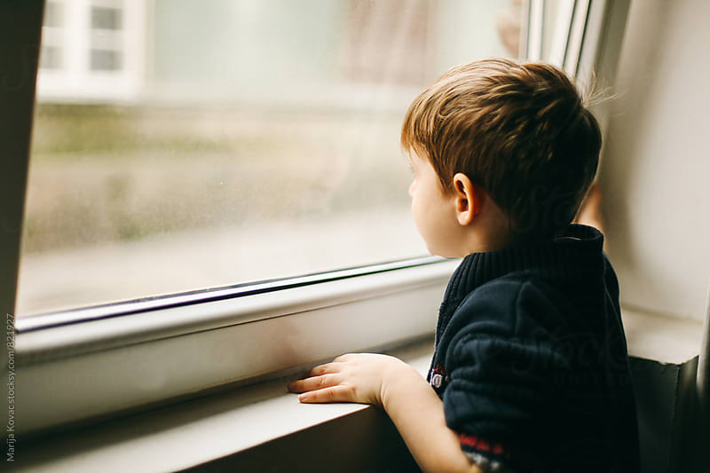 Boy looking through the window, horizontal by Marija Kovac for Stocksy United
