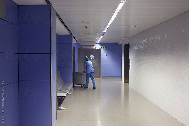 Medical staff at work in a hospital corridor by Miquel Llonch for Stocksy United