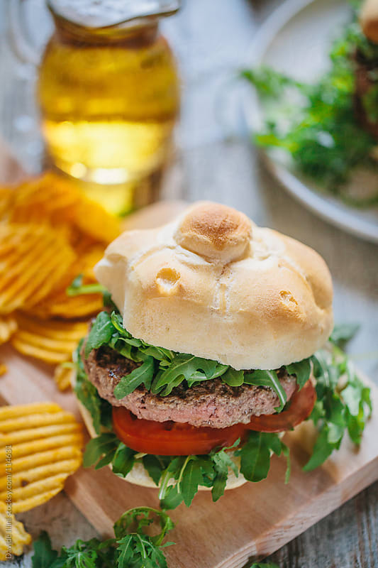 Hamburger with tomatoes and arugula by Davide Illini for Stocksy United