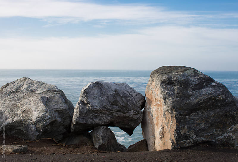 Rocks along the coast with a rock formation by Carolyn Lagattuta for Stocksy United