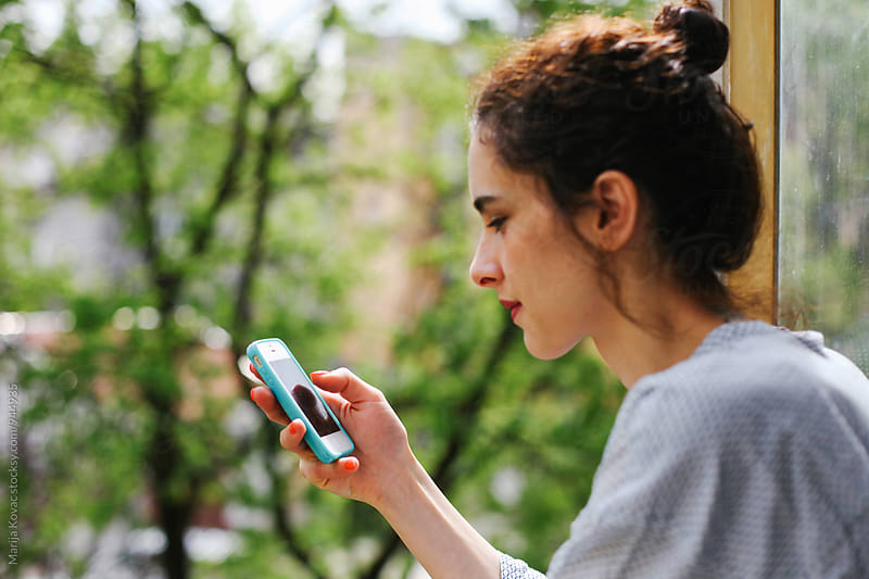 Young woman browsing on her smart phone by Marija Kovac for Stocksy United