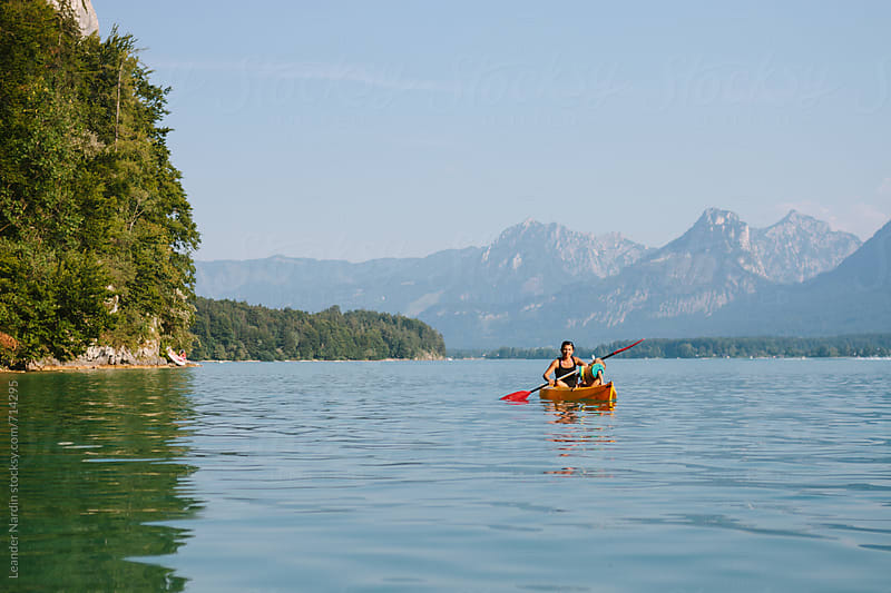 mother and son canoeing on a lake with mountains in the back by Leander Nardin for Stocksy United