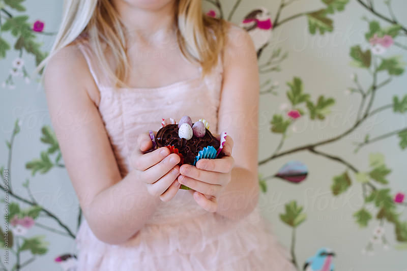 A little girl holding an Easter cupcake. by Helen Rushbrook for Stocksy United