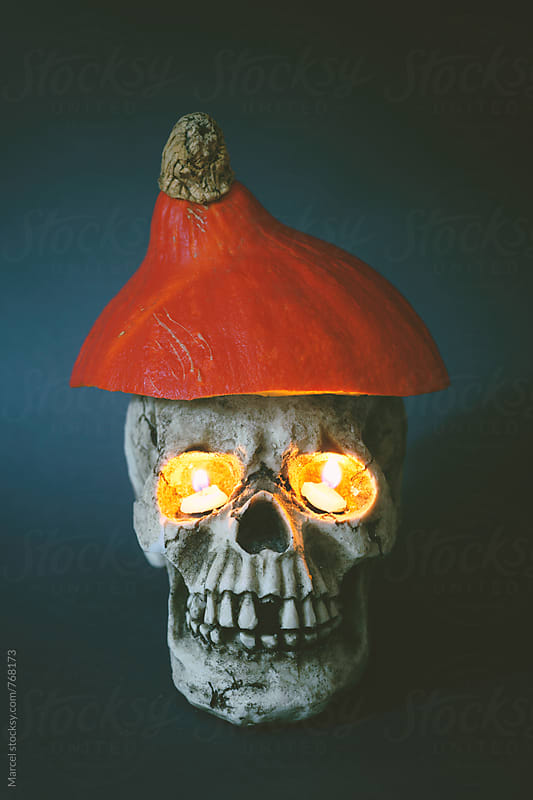 Skull with pumpkin hat and burning eyes by Marcel for Stocksy United