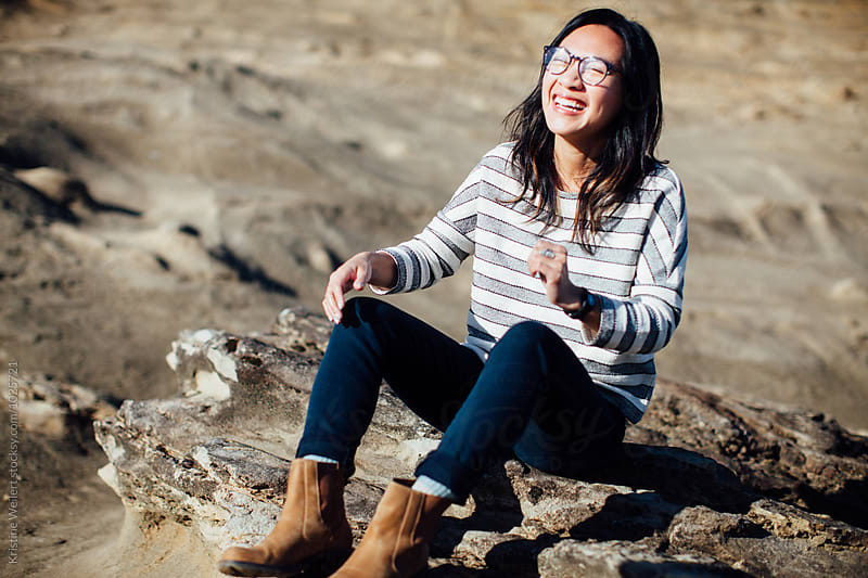 Happy, hip vietnamese woman laughing while sitting on a rock outdoors by Kristine Weilert for Stocksy United