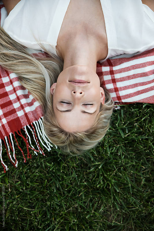 Woman lying on the grass by Ivan Solis for Stocksy United