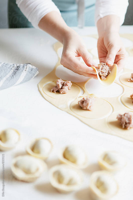 Woman making meat dumplings by Ellie Baygulov for Stocksy United