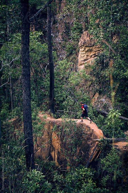 Man in red jacket running on narrow jungle trail. by Soren Egeberg for Stocksy United