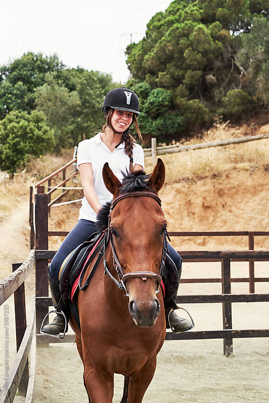 Smiling teen brunette in helmet riding horse in fence by Guille Faingold for Stocksy United