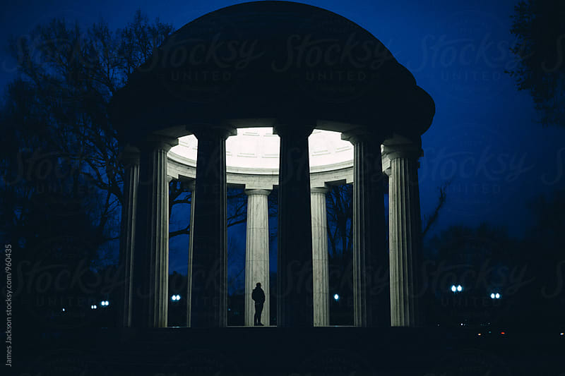 Lone figure at sunrise in center of marble rotunda by James Jackson for Stocksy United