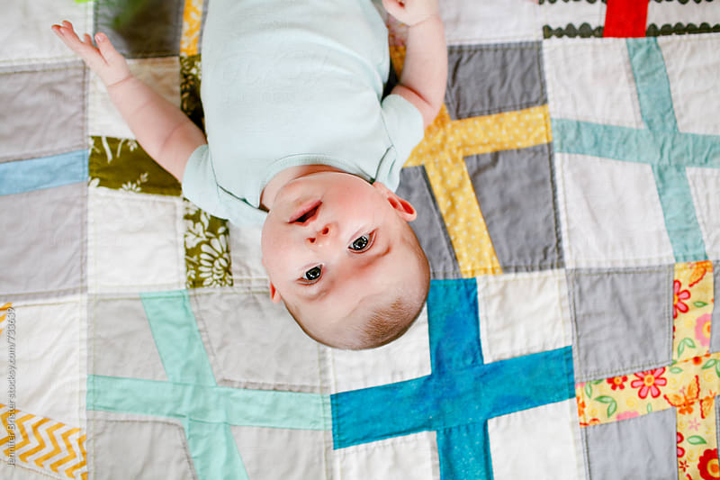 Baby looking at camera by Jen Brister for Stocksy United