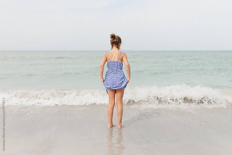 Preteen girl holding dress up so that it doesn't get wet in the ocean by Amanda Worrall for Stocksy United