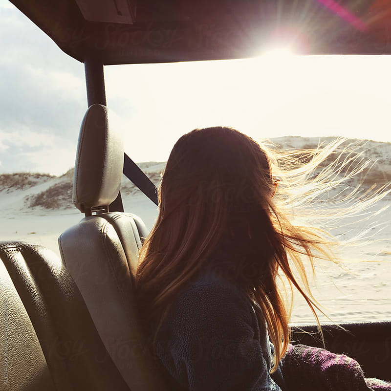 Teenage Girl Riding In An Open Jeep With The Wind In Her Hair by ALICIA BOCK for Stocksy United
