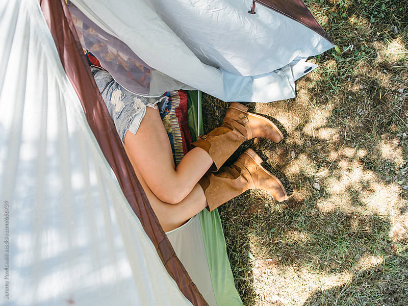 Girl in boots laying in tent. by Jeremy Pawlowski for Stocksy United