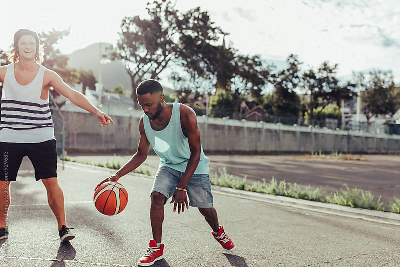 Two young men playing basketball by Jacob Lund for Stocksy United