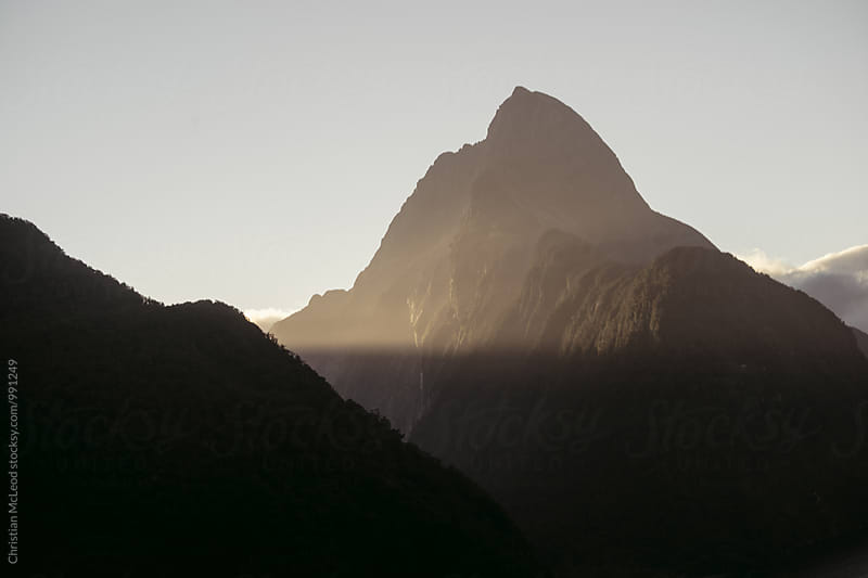 Milford Sound cliff being wrapped by sun rays in the evening.