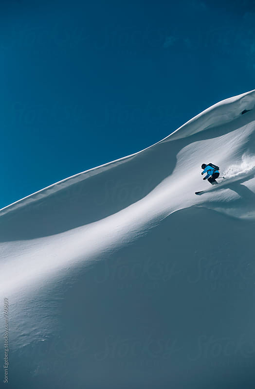 Male skier freeriding steep powder slope in the mountains of Austria by Søren Egeberg Photography for Stocksy United