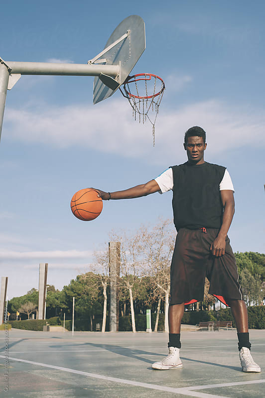 Brutal basketball player with ball in his hand above ground. by Guille Faingold for Stocksy United