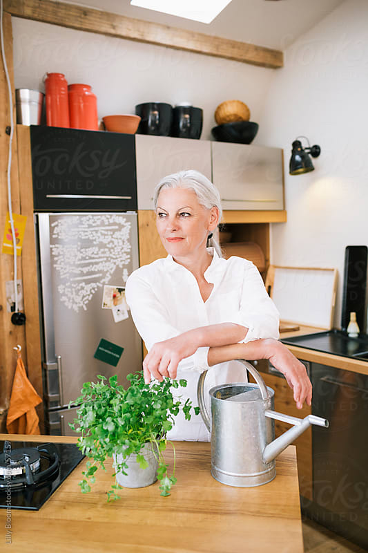 Senoir woman in her kitchen with a cilantro plant and watering can. by Lilly Bloom for Stocksy United
