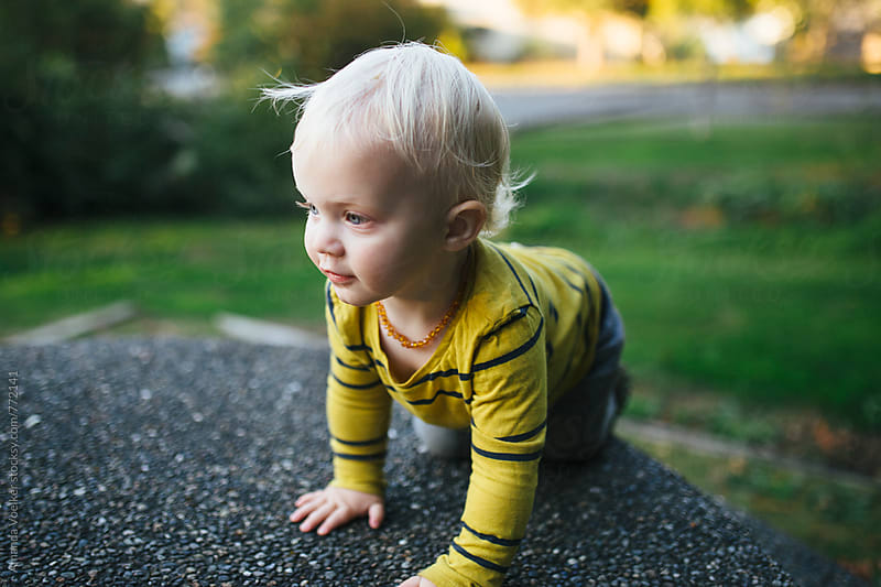 Partial Profile of a toddler boy climbing on an outdoor table by Amanda Voelker for Stocksy United