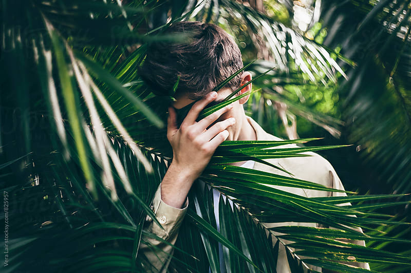 Young man hiding his face with hand while standing in palm trees forest by Vera Lair for Stocksy United