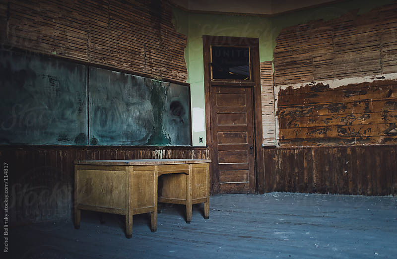 An old desk sits in the middle of an abandoned classroom by Rachel Bellinsky for Stocksy United