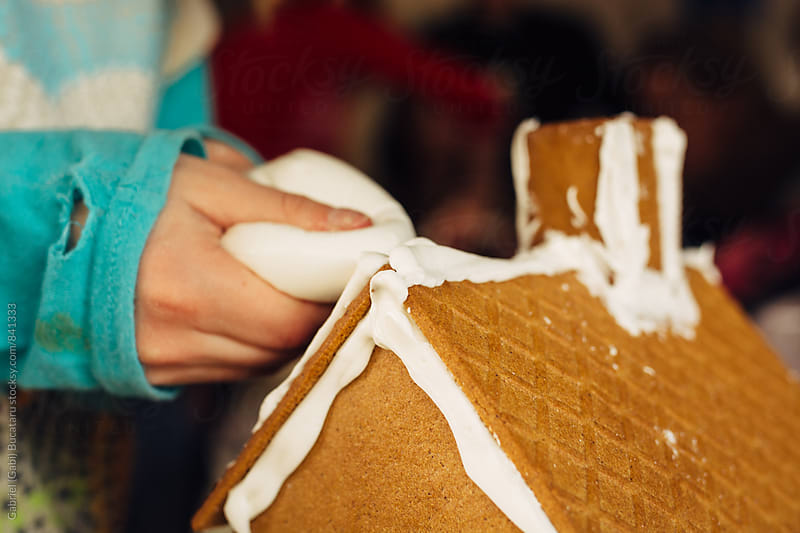 Young child's hands putting frosting on a gingerbread house by Gabriel (Gabi) Bucataru for Stocksy United