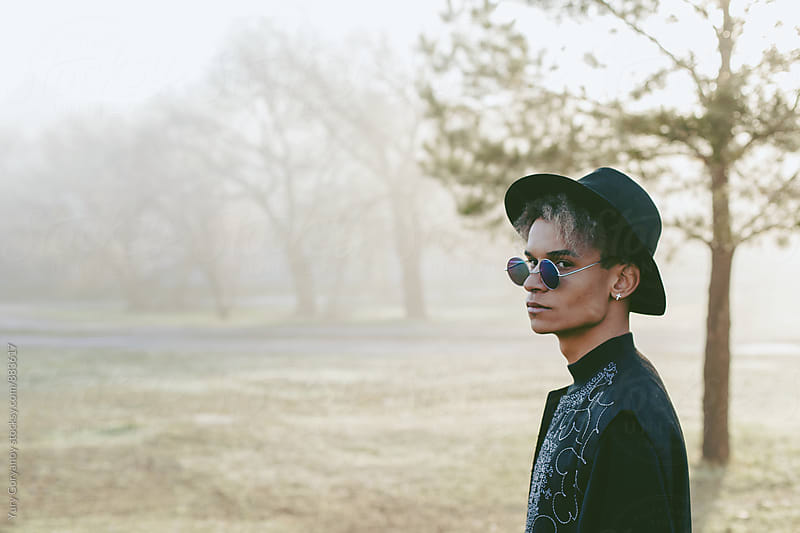 Portrait of young man in a hat and glasses in the trees by Yury Goryanoy for Stocksy United