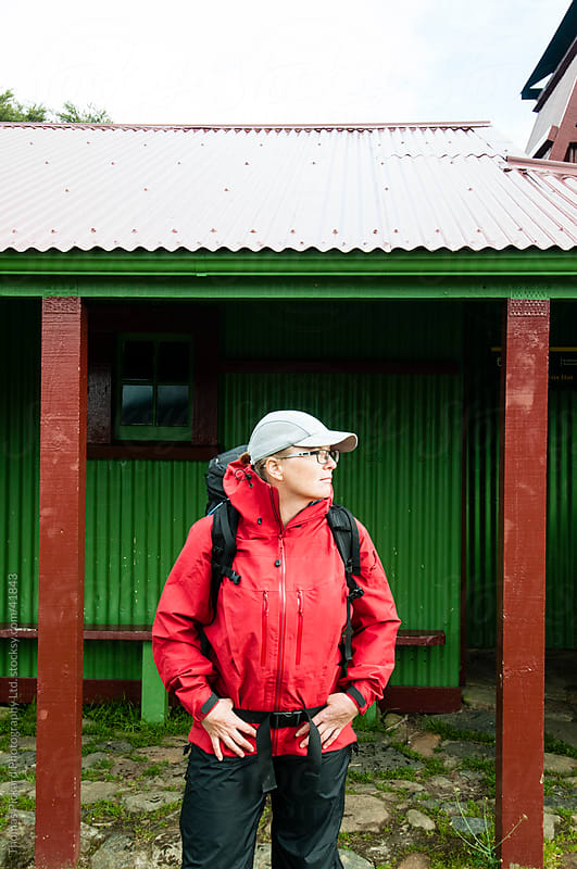 Female walker standing outside Gouland Downs Hut, Heaphy Track, Kahurangi National Park, New Zealand. by Thomas Pickard for Stocksy United
