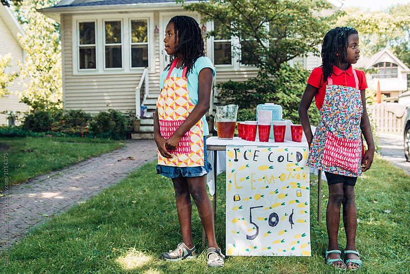 Two black girl by a lemonade stand waiting for customers by Gabriel (Gabi) Bucataru for Stocksy United