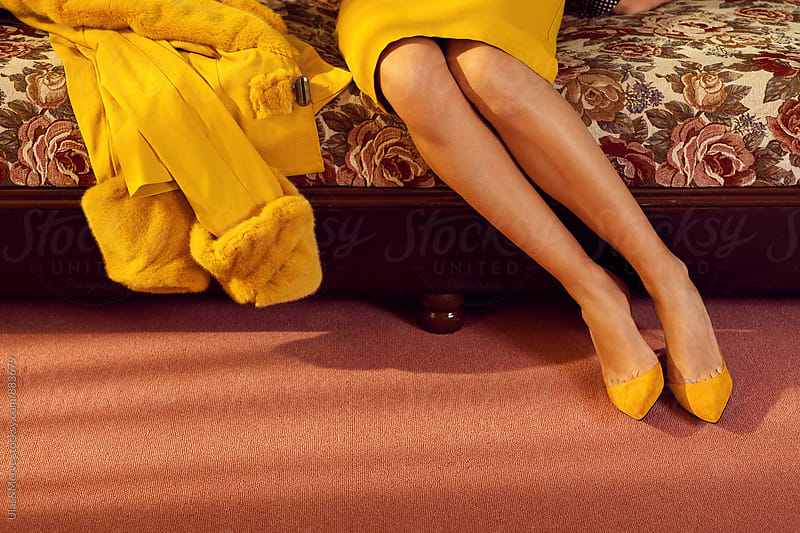 legs of a young lady with yellow skirt by Ulaş and Merve for Stocksy United