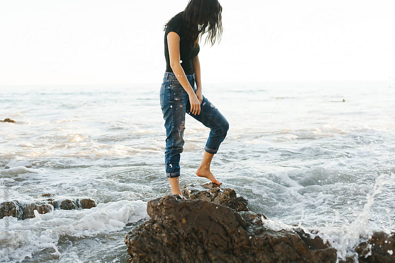 Cute Young Woman On Beach Standing on a Rock by Caleb Thal for Stocksy United