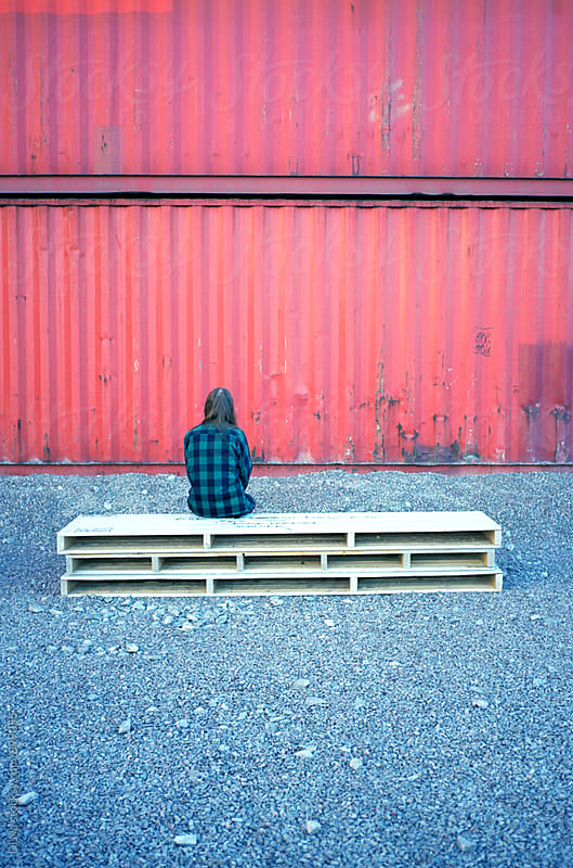 Young man sitting on a wooden bench with  red container on the background by Dina Lun for Stocksy United