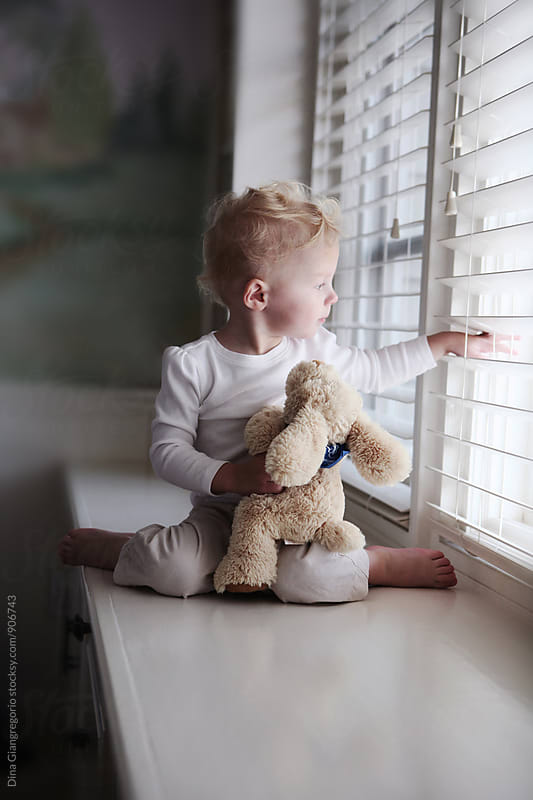Toddler Sitting On Window Seat Looking Outside by Dina Giangregorio for Stocksy United