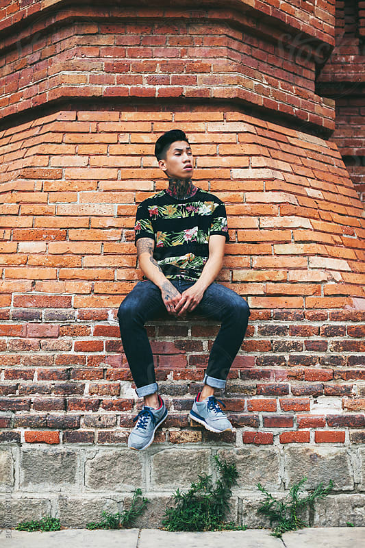 Portrait of a tattooed man sitting in front of a brick wall. by BONNINSTUDIO for Stocksy United