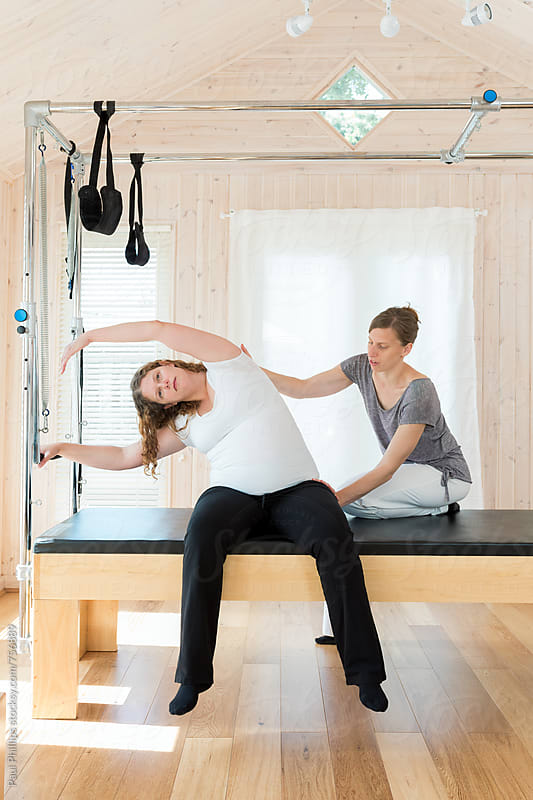 Pilates exercise carried out by a pregnant woman under supervision of a trained instructor by Paul Phillips for Stocksy United