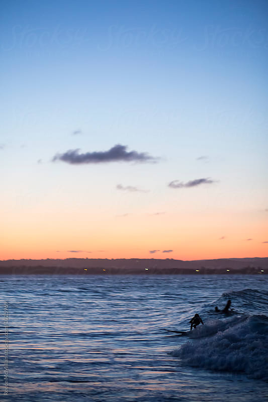 A surfer catches a sunset wave by Reece McMillan for Stocksy United