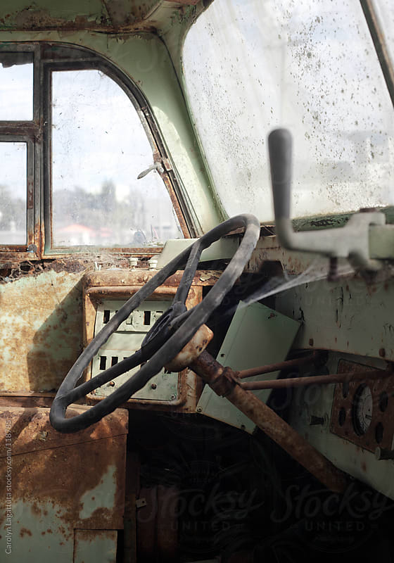 The inside of a neglected and rusty bus by Carolyn Lagattuta for Stocksy United