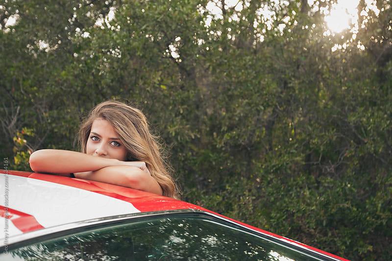 Woman resting her head on classic car by Geoffrey Hammond for Stocksy United