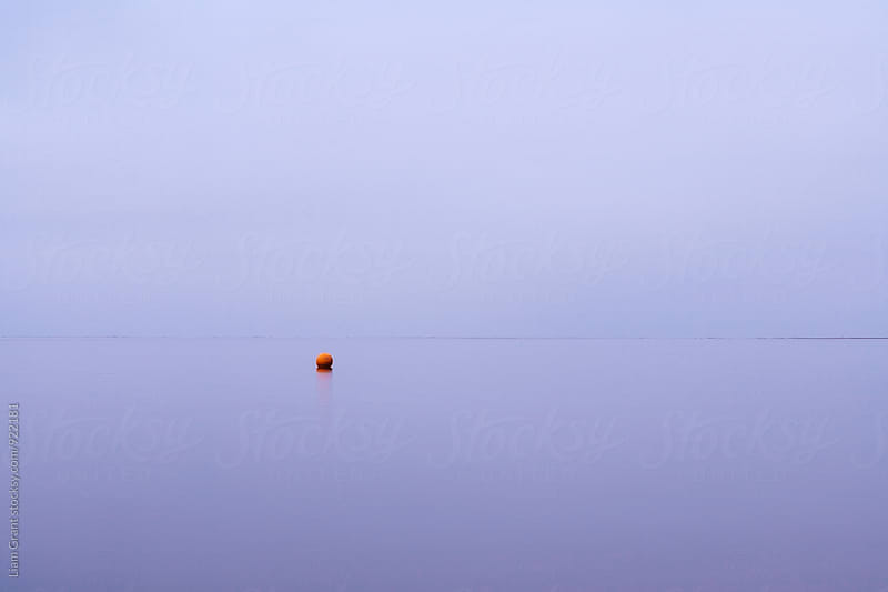 Cloudy sky a bouy reflected in a calm ocean at twilight. Norfolk, UK. by Liam Grant for Stocksy United