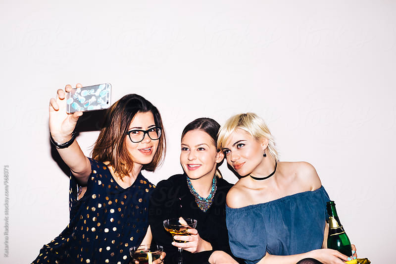 Three Girlfriends Taking Selfies at the Party by Katarina Radovic for Stocksy United