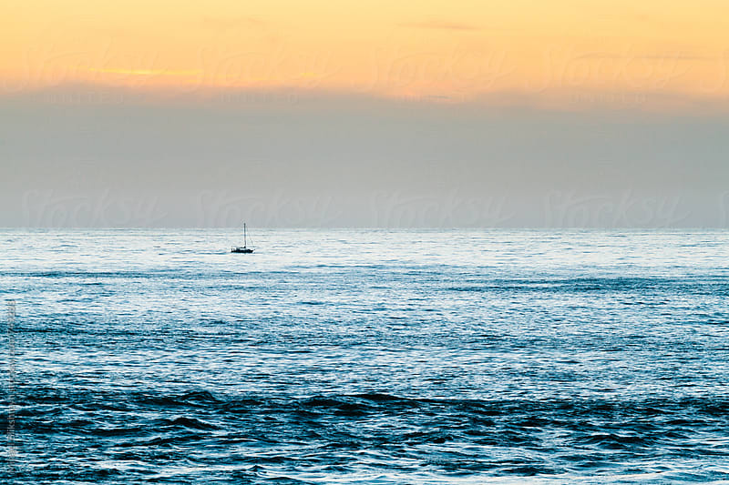 Lone sailboat in the calm, open ocean at sunset by Mihael Blikshteyn for Stocksy United