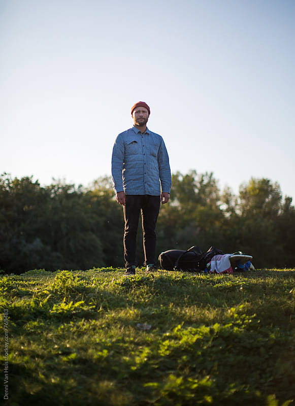 Men standing on grass with his stuff next to him on the ground by Denni Van Huis for Stocksy United